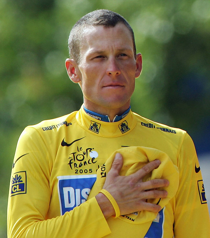 . Discovery Channel team rider Lance Armstrong of the U.S. stands with his hand on his heart during the playing of national anthems after he won his seventh straight Tour de France in Paris on July 24, 2005. REUTERS/Francois Lenoir