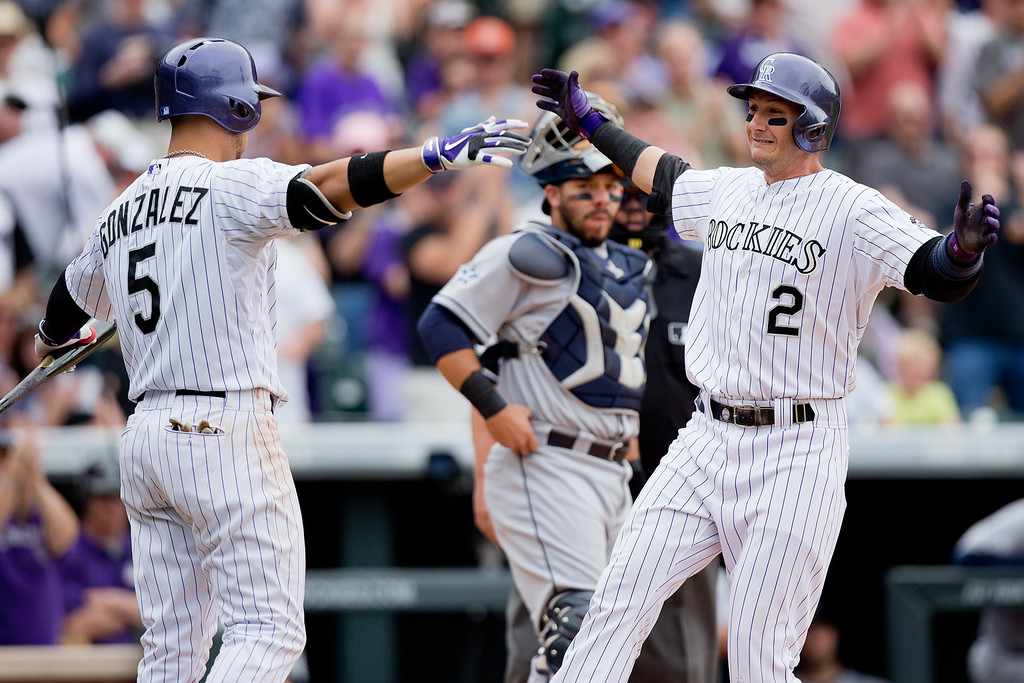 . Troy Tulowitzki #2 of the Colorado Rockies celebrates his solo home run with Carlos Gonzalez #5 as Rene Rivera #44 of the San Diego Padres looks on during the fifth inning at Coors Field on May 18, 2014 in Denver, Colorado. The Rockies defeated the Padres 8-6 in 10 innings. (Photo by Justin Edmonds/Getty Images)