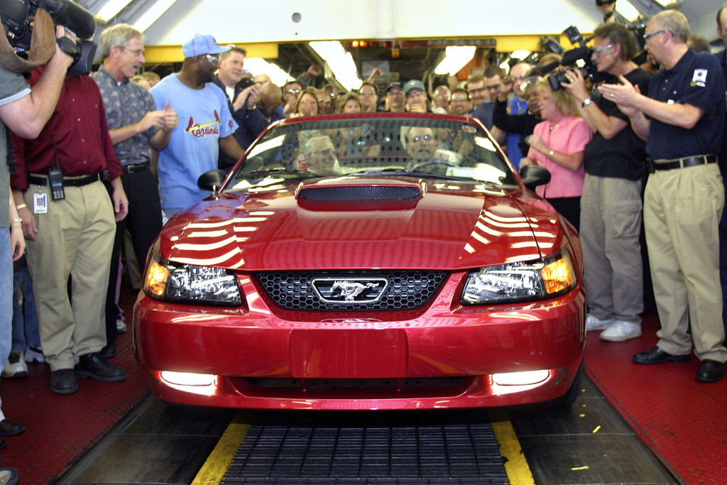 . The last Ford Mustang built at the Dearborn Assembly Plant rolls off the line May 10, 2004 in Dearborn, Michigan. The plant opened in 1918. Sitting in the passenger seat is Oscar Hovsapian who drove the first Mustang off the line in 1964.  (Photo by Bill Pugliano/Getty Images)