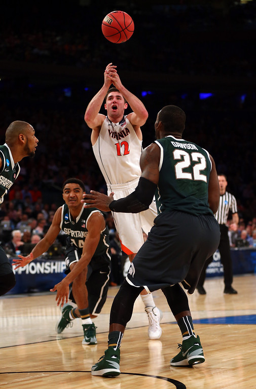 . Joe Harris #12 of the Virginia Cavaliers loses the ball against Branden Dawson #22 of the Michigan State Spartans during the regional semifinal of the 2014 NCAA Men\'s Basketball Tournament at Madison Square Garden on March 28, 2014 in New York City.  (Photo by Elsa/Getty Images)