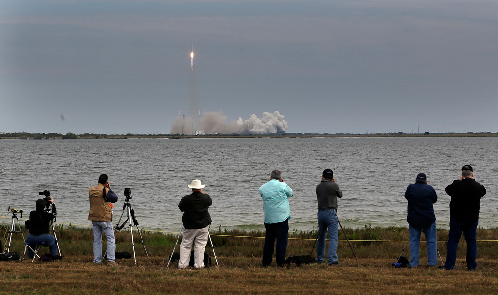 . People photograph the Falcon 9 SpaceX rocket as it lifts off from launch complex 40 at the Cape Canaveral Air Force Station in Cape Canaveral, Fla. on Friday, March 1, 2013. The rocket is transporting the Dragon capsule to the International Space Station containing more than a ton of food, tools, computer hardware and science experiments. (AP Photo/John Raoux)