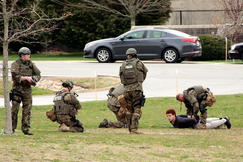 . State Police arrest a man walking at the UMASS-Dartmouth campus during their sweep of the university Friday, April 19, 2013, in Dartmouth, Mass.  (AP Photo/Standard Times, Peter Pereira)
