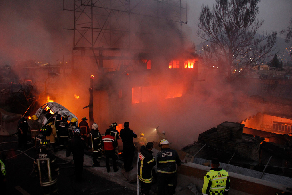 . Firefighters work as a house burns after a gas tanker truck exploded on the highway in front of the house in the Mexico City suburb of Ecatepec, early Tuesday, May 7, 2013.  The blast killed and injured dozens, according to the Citizen Safety Department of Mexico State. Officials did not rule out the possibility the death toll could rise as emergency workers continued sifting through the charred remains of vehicles and homes built near the highway on the northern edge of the metropolis. (AP Photo/Gabriela Sanchez)