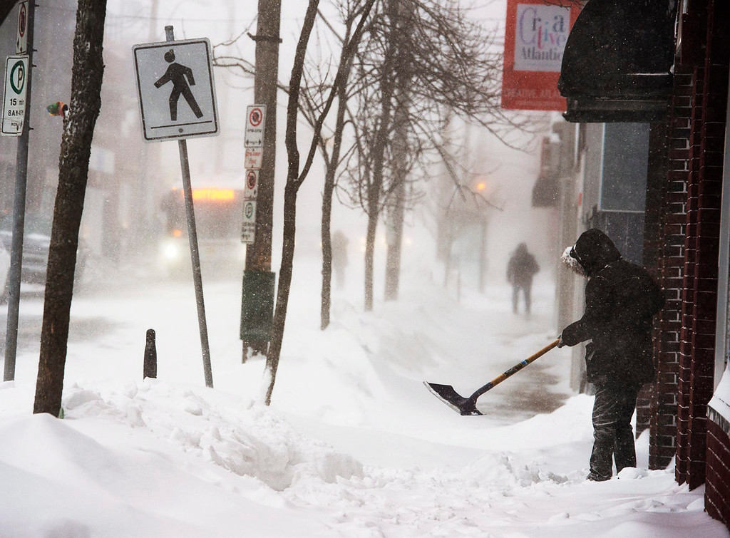 . A man clears a sidewalk in blizzard conditions in Halifax, Nova Scotia, Friday, Jan. 3, 2014. The region is in the grip of unseasonably cold temperatures with heavy snow and high winds. (AP Photo/The Canadian Press,Andrew Vaughan)