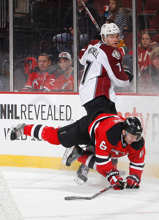 . John Mitchell #7 of the Colorado Avalanche sends Andy Greene #6 of the New Jersey Devils to the ice during the third period in an NHL hockey game at Prudential Center on February 3, 2014 in Newark, New Jersey.  Colorado won 2-1 in overtime.  (Photo by Paul Bereswill/Getty Images)