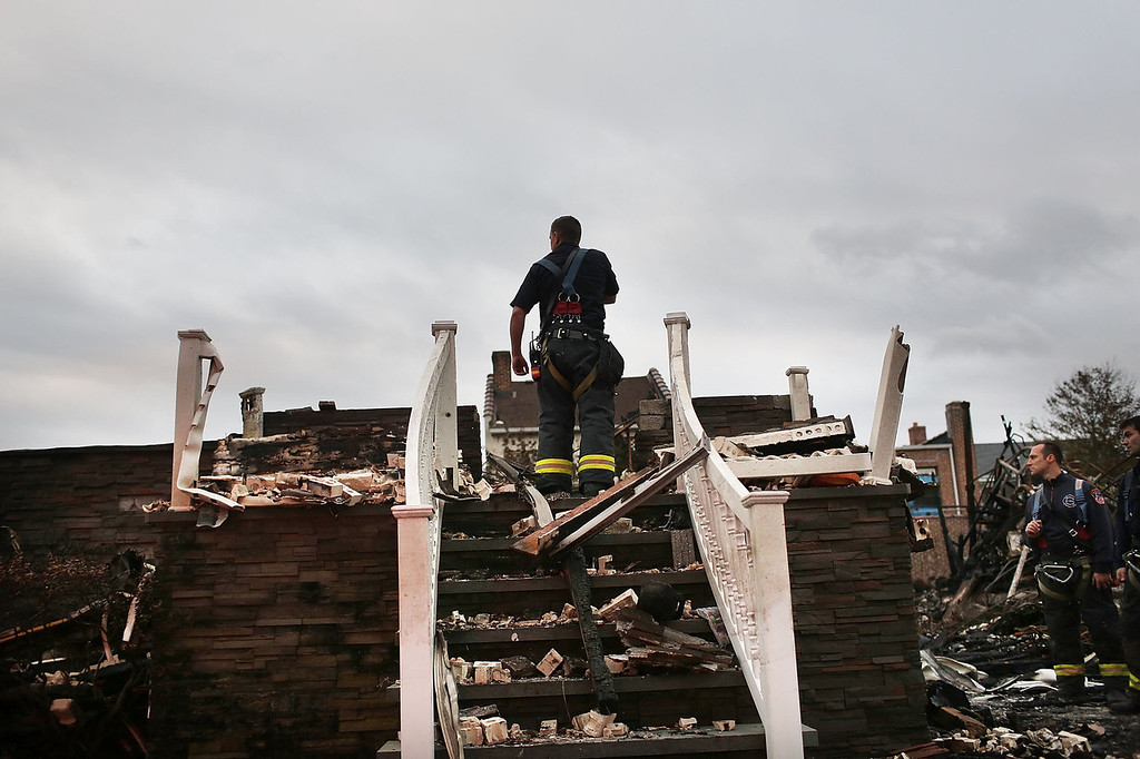 . A firefighter stands in the remains of a home in the Rockaway neighborhood destroyed by fire during Hurricane Sandy on October 31, 2012 in the Queens borough of New York City. With the death toll currently at 55 and millions of homes and businesses without power, the US east coast is attempting to recover from the affects of floods, fires and power outages brought on by Hurricane Sandy. JFK airport in New York and Newark airport in New Jersey expect to resume flights on Wednesday morning and the New York Stock Exchange commenced trading after being closed for two days.  (Photo by Spencer Platt/Getty Images)