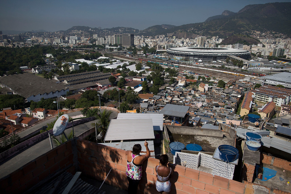 . In this Wednesday, June 4, 2014 photo, women visit on a rooftop where they can see Maracana stadium from the Mangueira slum in Rio de Janeiro, Brazil. With tickets to the World Cup tournament expensive and hard to come by, the gulf between Mangueira and Maracana is almost impassable. (AP Photo/Leo Correa)