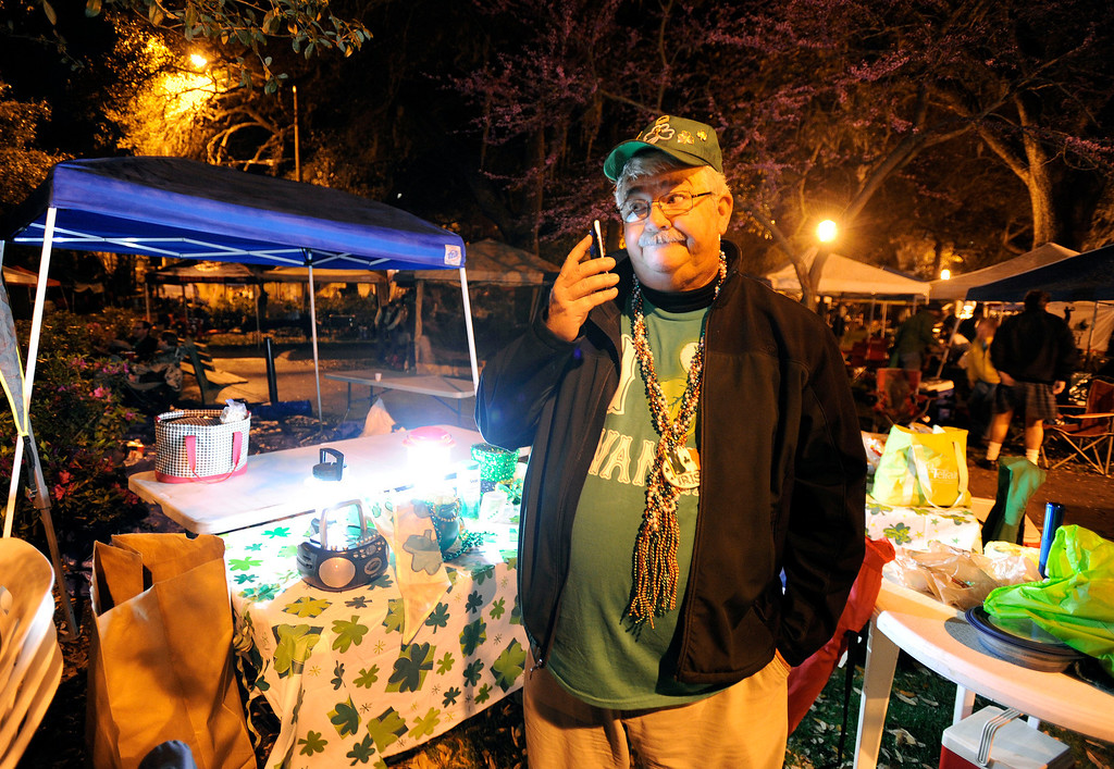 . Kevin Rippman, of Savannah, Ga., checks in with his wife on the phone after setting up before dawn in Lafayette Square before Savannahís 189-year-old St. Patrickís Day parade, Saturday, March 16, 2013, in Savannah, Ga. St. Patrick\'s Day falls on March 17, which is Sunday. But a number of cities, including Savannah, New York and Chicago are all holding parades Saturday to take advantage of the full weekend. (AP Photo/Stephen Morton)