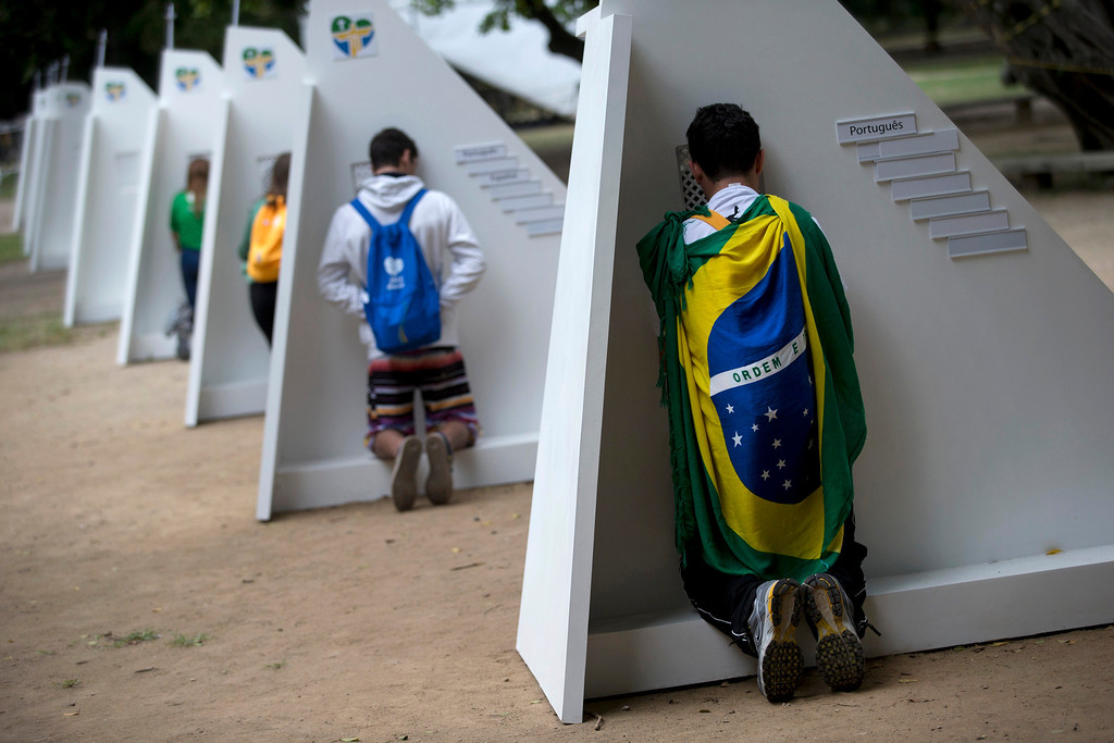 . Catholics kneel at portable confessionals set up in Quinta da Boa Vista park during World Youth Day events in Rio de Janeiro, Brazil, Tuesday, July 23, 2013. The pope is here on a seven-day visit meant to fan the fervor of the faithful around the globe. (AP Photo/Silvia Izquierdo)