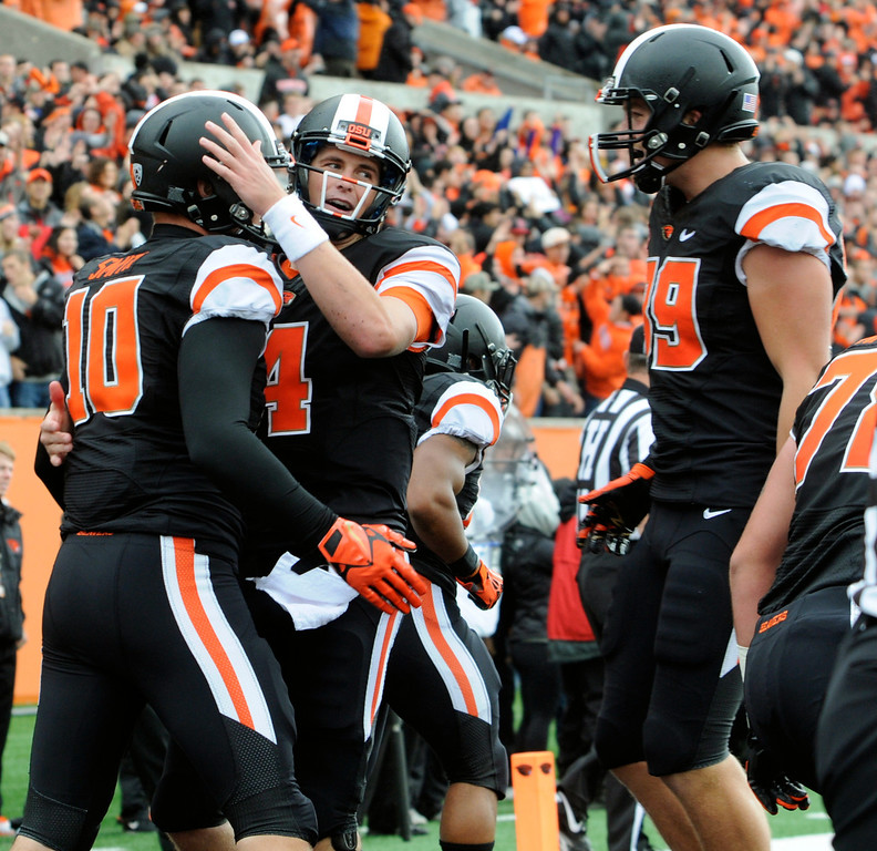 . Oregon State\'s quarterback Sean Mannion (4) congratulates Caleb Smith (10) on his touchdown reception against Colorado in the first half of an NCAA college football game on Saturday, Sept 28, 2013, in Corvallis, Ore. (AP Photo/Greg Wahl-Stephens)