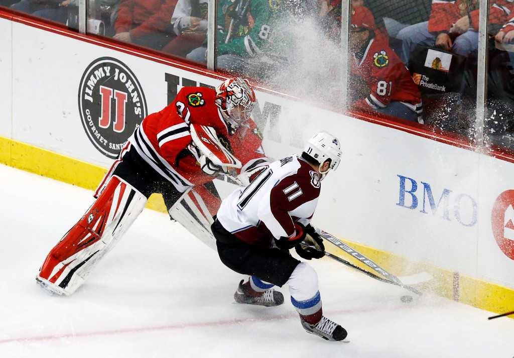 . Chicago Blackhawks goalie Antti Raanta (31) and Colorado Avalanche left wing Jamie McGinn battle for a loose puck during the first period of an NHL hockey game Friday, Dec. 27, 2013, in Chicago. (AP Photo/Charles Rex Arbogast)