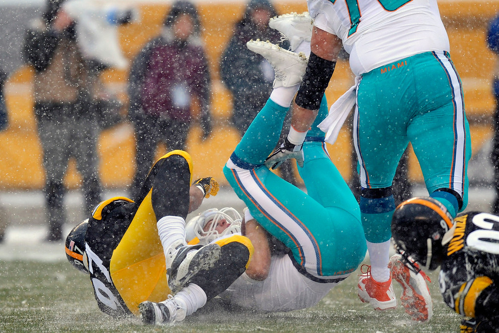 . Miami Dolphins quarterback Ryan Tannehill, center, is sacked by Pittsburgh Steelers defensive end Cameron Heyward (97) in the first quarter of an NFL football game in Pittsburgh, Sunday, Dec. 8, 2013. (AP Photo/Don Wright)