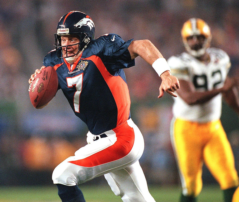 . Denver Broncos quarterback John Elway scrambles for an eight-yard gain in the second half of Super Bowl XXXII against the Green Bay Packers in San Diego. In the background is Green Bay Packers defender Reggie White. (DOUG COLLIER/AFP/Getty Images)