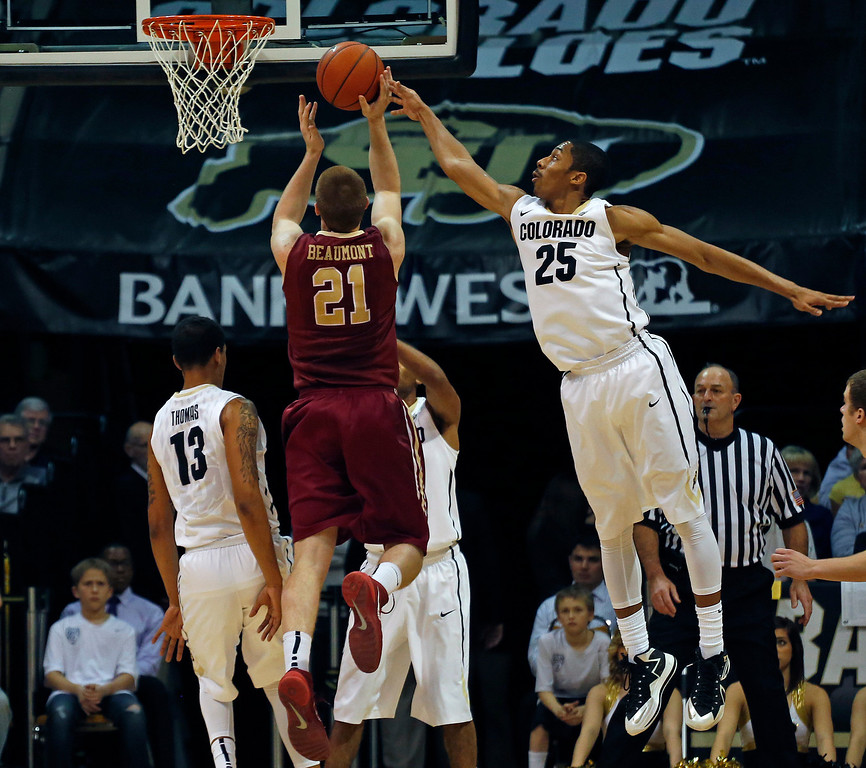 . Colorado\'s Spencer Dinwiddie, right, tips away a shot by Elon\'s Ryley Beaumont during the first half of an NCAA college basketball game in Boulder, Colo., Friday, Dec. 13, 2013. (AP Photo/Brennan Linsley)