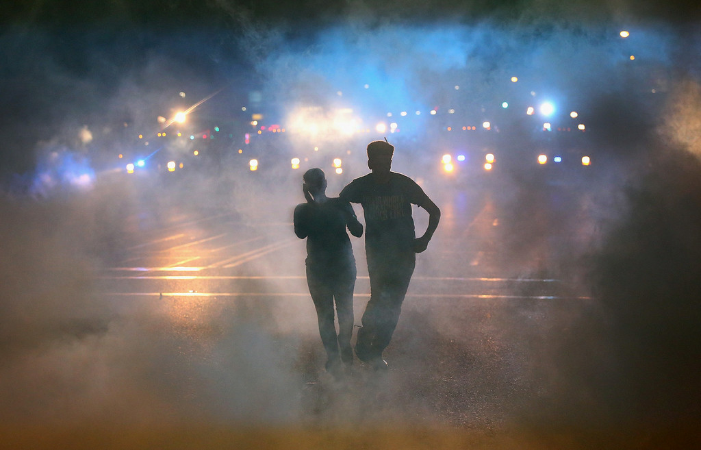 . A woman is helped from the street after becoming overcome by tear gas during a demonstration over the killing of teenager Michael Brown by a Ferguson police officer on August 17, 2014 in Ferguson, Missouri. Despite the Brown family\'s continued call for peaceful demonstrations, violent protests have erupted nearly every night in Ferguson since his August 9, death.  (Photo by Scott Olson/Getty Images)