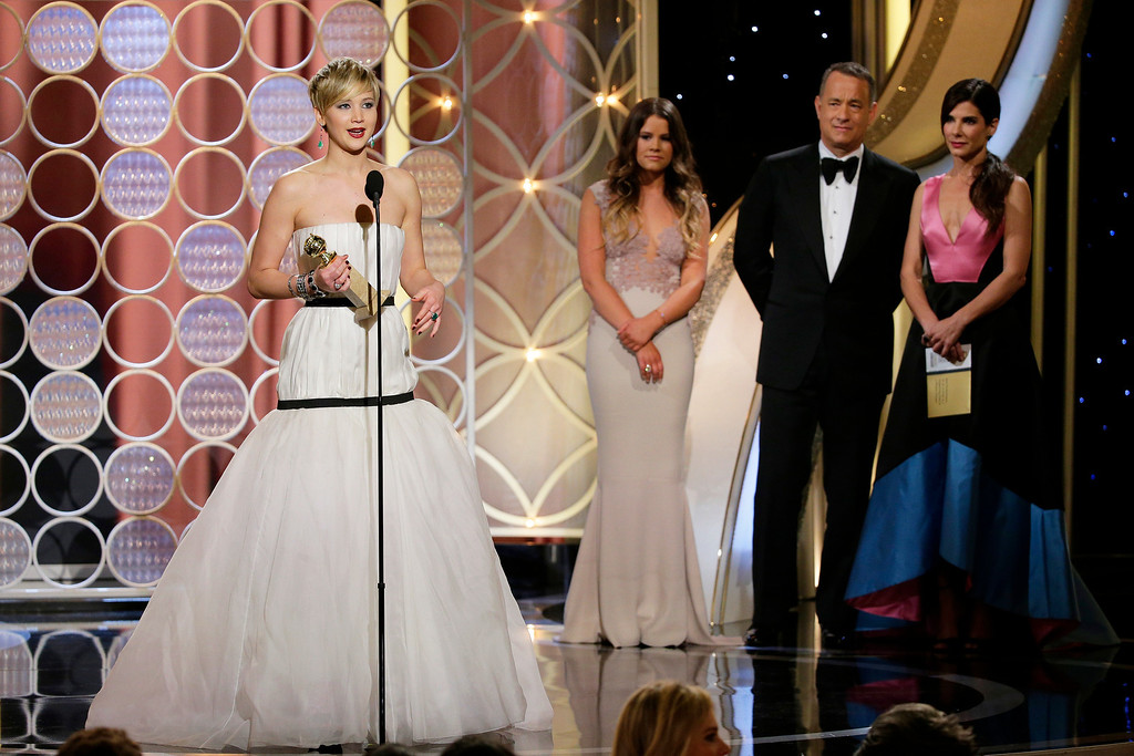 ". Jennifer Lawrence, left, accepts the award for best supporting actress in a motion picture for her role in ""American Hustle,\"" as presenters Sandra Bullock, right, and Tom Hanks, second right, look on during the 71st annual Golden Globe Awards at the Beverly Hilton Hotel on Sunday, Jan. 12, 2014, in Beverly Hills, Calif. (AP Photo/NBC, Paul Drinkwater)"