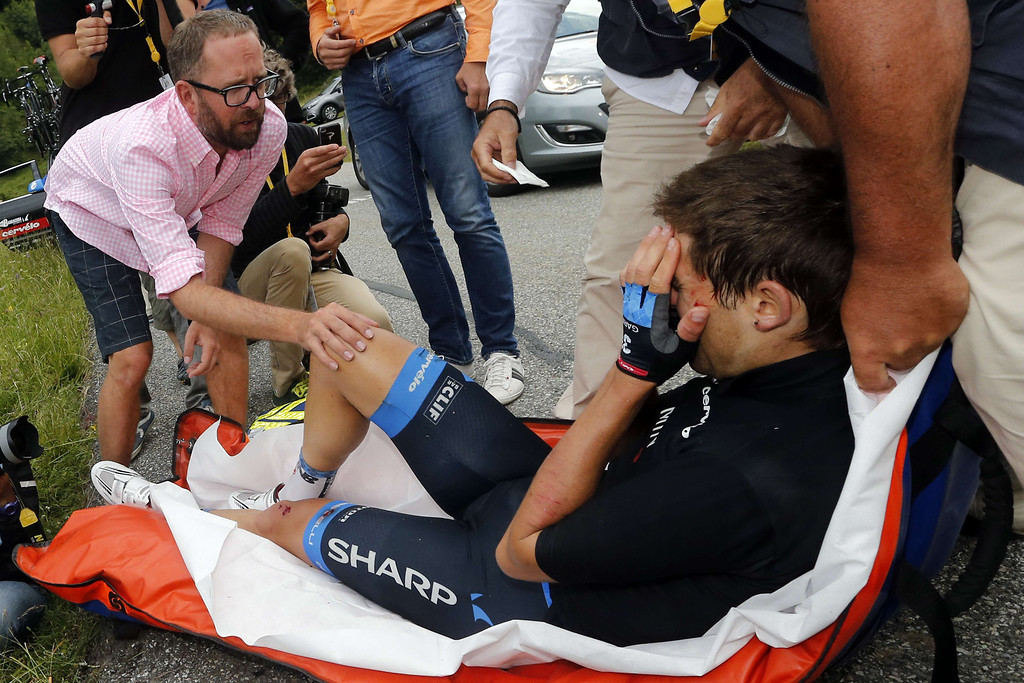 . Jonathan Vaughters (L), General Manager of US Garmin-Sharp cycling team, speaks to New Zealand\'s Jack Bauer as he receives medical assistance on a stretcher after falling during the 204.5 km nineteenth stage of the 100th edition of the Tour de France cycling race on July 19, 2013 between Bourg-d\'Oisans and Le Grand-Bornand, French Alps.  AFP PHOTO / JOEL SAGET/AFP/Getty Images