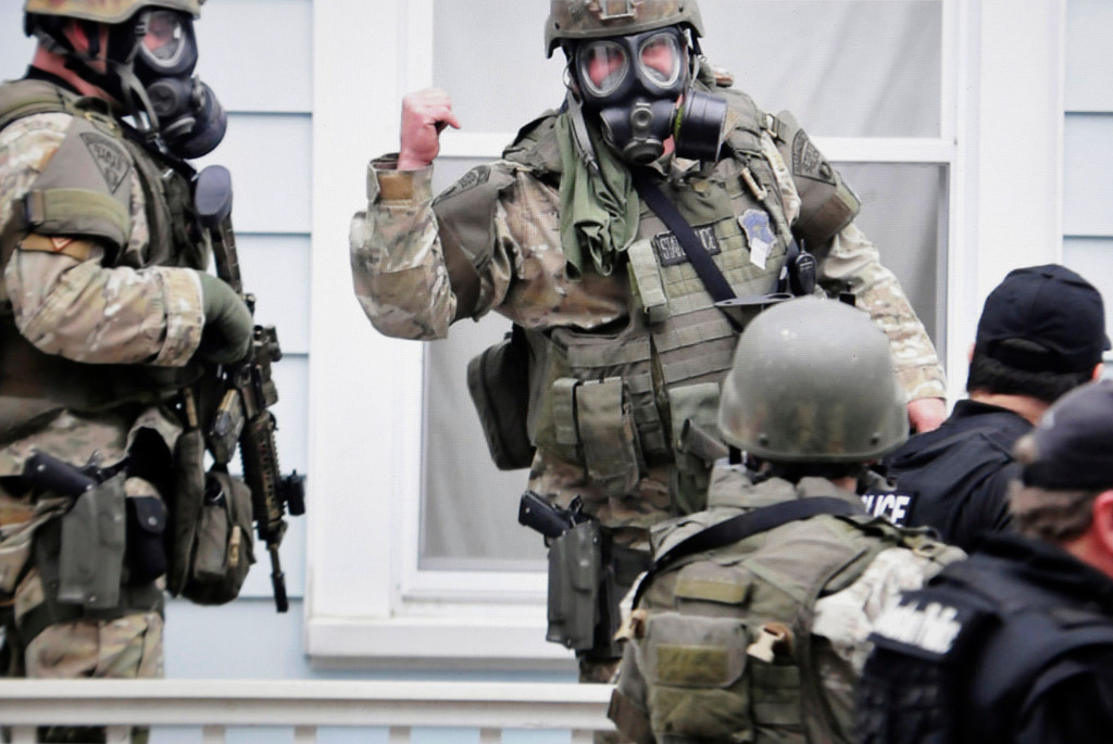 . In this Friday, April 19, 2013 Massachusetts State Police photo, state troopers dressed in protective gear hold weapons as they stand near a home, in Watertown, Mass. Later that night, 19-year-old Boston Marathon bombing suspect Dzhokhar Tsarnaev was captured. (AP Photo/Massachusetts State Police, Sean Murphy)
