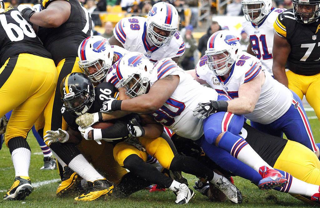 . Le\'Veon Bell #26 of the Pittsburgh Steelers is tackled by Alan Branch #90 and Kyle Williams #95 of the Buffalo Bills during the game on November 10, 2013 at Heinz Field in Pittsburgh, Pennsylvania.  (Photo by Justin K. Aller/Getty Images)