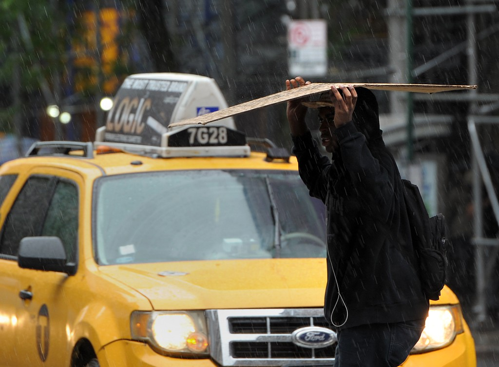 . A man on Lexingon Avenue uses a piece of cardboard as he crosses East 86th Street in a heavy rain June 13, 2013 in New York as a severe storm affects the northeastern U.S.  AFP PHOTO/Stan  HONDA/AFP/Getty Images