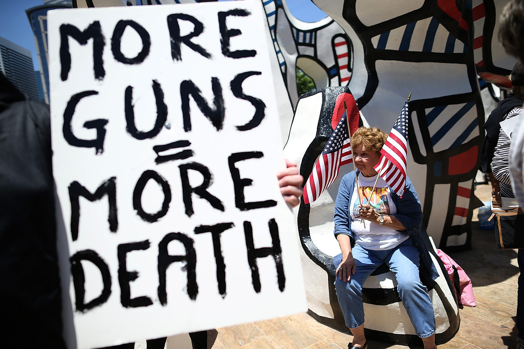 . HOUSTON, TX - MAY 04:  A protestor holds American flags during a demonstration in favor of gun regulation outside of the 2013 NRA Annual Meeting and Exhibits at the George R. Brown Convention Center on May 4, 2013 in Houston, Texas.  More than 70,000 peope are expected to attend the NRA\'s 3-day annual meeting that features nearly 550 exhibitors, gun trade show and a political rally. The Show runs from May 3-5.  (Photo by Justin Sullivan/Getty Images)