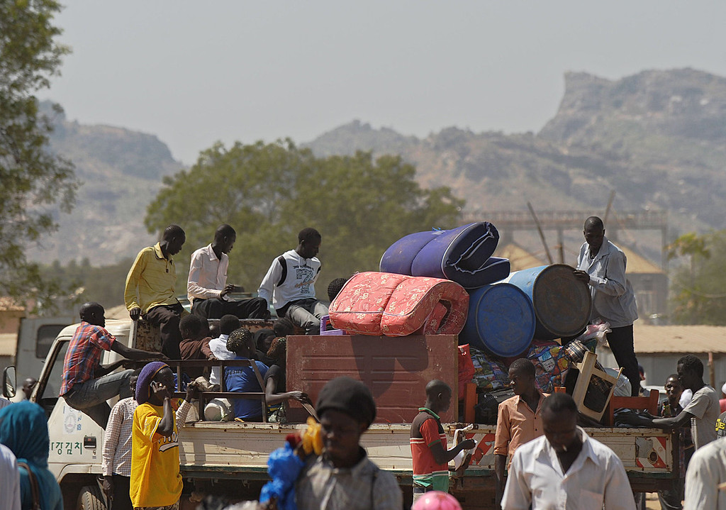 . Residents of Juba with their belongings pile onto a truck heading out of the city on December 21, 2013 where tension remains high fueling an exodus of both local and foreign residents from the south Sudanese capital. Brutal fighting in South Sudan has reopened deep-rooted ethnic divisions, forcing tens of thousands of terrified residents to seek shelter at UN bases or flee in fear of attacks. United Nations peacekeepers are currently sheltering over 35,000 civilians in various bases across the country, many belonging to the minority ethnic group in their respective areas. AFP PHOTO / TONY KARUMBATONY KARUMBA/AFP/Getty Images