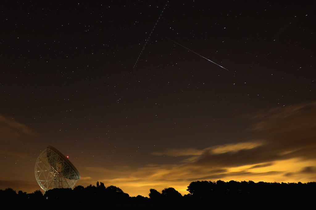 . HOLMES CHAPEL, UNITED KINGDOM - AUGUST 13:  A Perseid meteor streaks across the sky over the Lovell Radio Telescope at Jodrell Bank on August 13, 2013 in Holmes Chapel, United Kingdom.The annual display, known as the Perseid shower because the meteors appear to radiate from the constellation Perseus in the northeastern sky, is a result of Earth\'s orbit passing through debris from the comet Swift-Tuttle.  (Photo by Christopher Furlong/Getty Images)