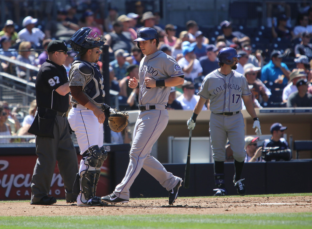 . Colorado Rockies\' Corey Dickerson, center, scores their first run on a double by Michael Cuddyer against the San Diego Padres in the third inning during the baseball game on Sunday, Sept. 8, 2013, in San Diego. (AP Photo/Don Boomer)