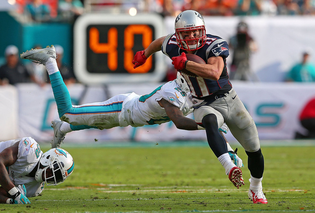 . Julian Edelman #11 of the New England Patriots escapes a tackle from Nolan Carroll #28 of the Miami Dolphins during a game  at Sun Life Stadium on December 15, 2013 in Miami Gardens, Florida.  (Photo by Mike Ehrmann/Getty Images)