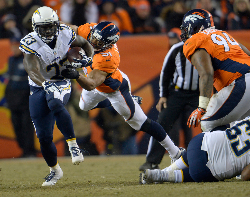 . San Diego Chargers running back Ronnie Brown (23) runs away with Denver Broncos middle linebacker Paris Lenon (51) holding on during the third quarter. The Denver Broncos vs. the San Diego Chargers at Sports Authority Field at Mile High in Denver on December 12, 2013. (Photo by Joe Amon/The Denver Post)