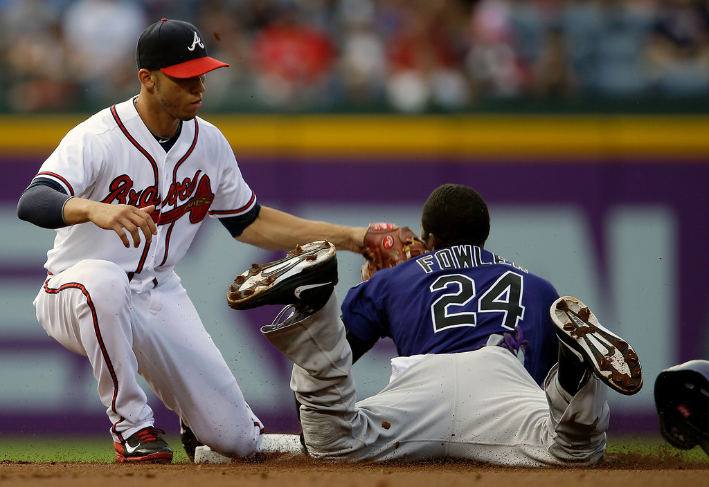 . Colorado Rockies\' Dexter Fowler (24) is tagged out by Atlanta Braves shortstop Andrelton Simmons, left, while trying to steal second base in the first inning of a baseball game in Atlanta, Wednesday,  July 31, 2013. (AP Photo/John Bazemore)