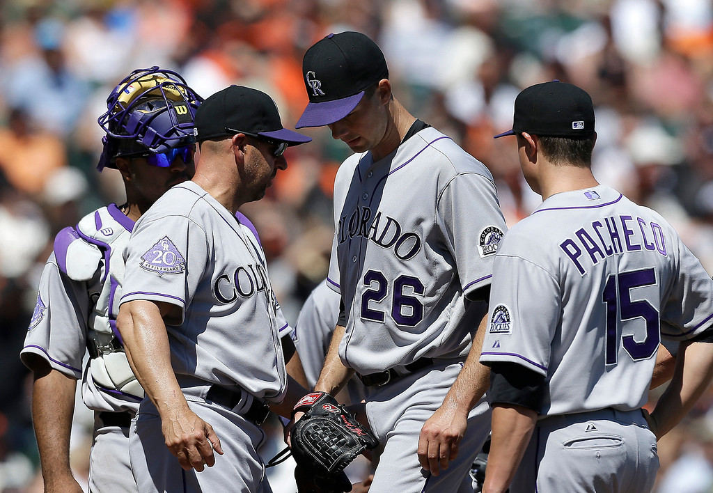 . Colorado Rockies pitcher Jeff Francis (26) is taken out for a relief pitcher by manager Walt Weiss, second from left, during the second inning of a baseball game against the San Francisco Giants in San Francisco, Wednesday, April 10, 2013. Catcher Wilin Rosario, left, and third baseman Jordan Pacheco (15) stand by. (AP Photo/Jeff Chiu)