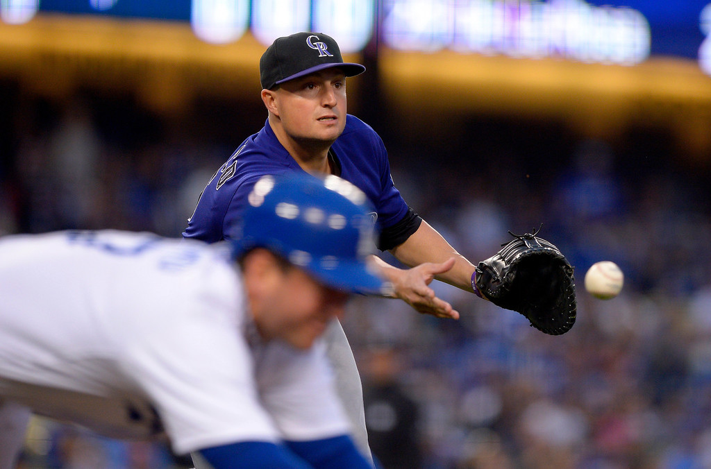 . Colorado Rockies first baseman Jordan Pacheco, right, tosses the ball to first as Los Angeles Dodgers\' Nick Punto dives in for a single during the first inning of their baseball game, Tuesday, April 30, 2013, in Los Angeles.   (AP Photo/Mark J. Terrill)
