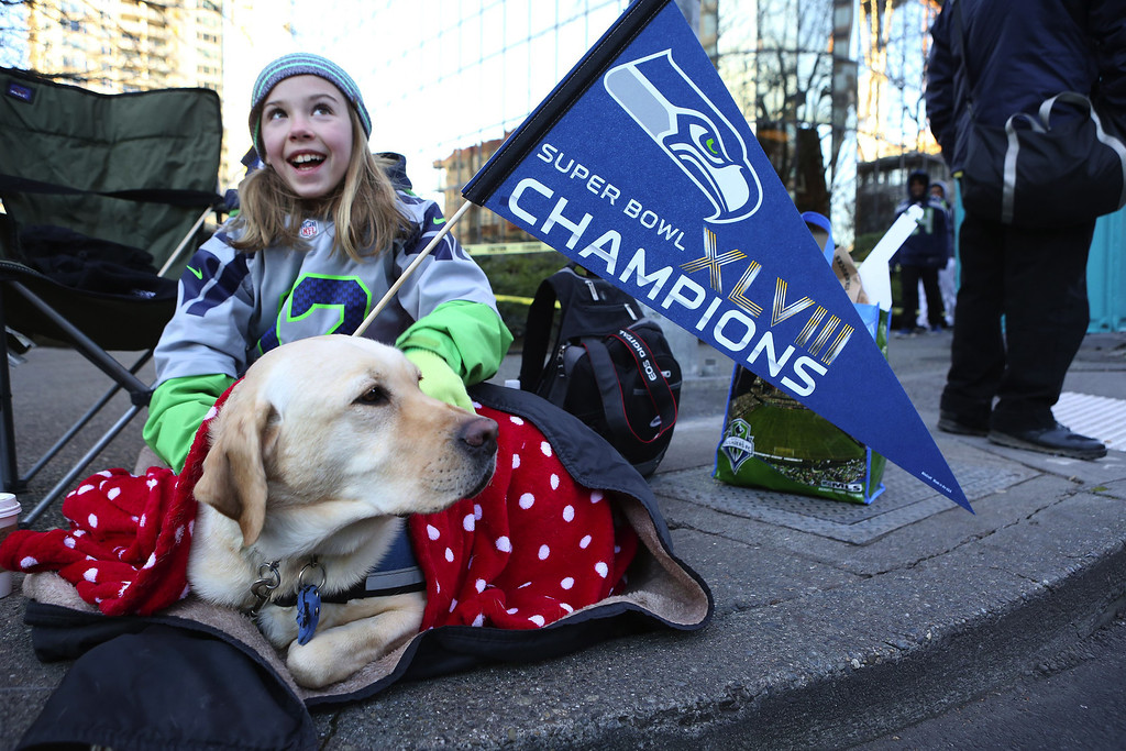 . Kaitlyn Steffy, 10, of Woodinville, Wash., sits with the family dog Tina waiting for the Super Bowl champions parade to begin Wednesday, Feb. 5, 2014, in Seattle. The Seahawks beat the Denver Broncos 43-8 in NFL football\'s Super Bowl XLVIII on Sunday. (AP Photo/The Seattle Times, Ken Lambert)