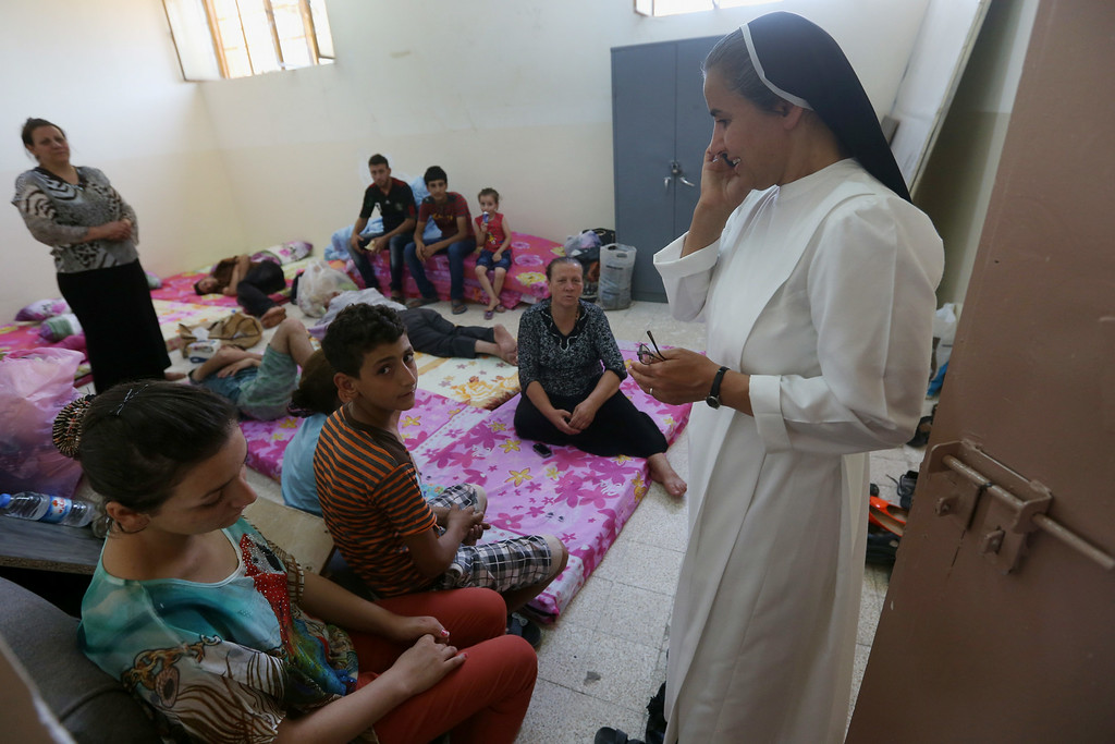 . An Iraqi nun, right, speaks on her cellphone as she visits displaced families who fled from Christian villages near Mosul province in Iraq, at a school which turned as a shelter for the displaced Christian families, in Ainkawa, a suburb of Irbil, with a majority Christian population, Iraq, Friday, June 27, 2014. Around 2,000 Christians had entered the Kurdish city of Irbil by Thursday morning, June 26. A Christian official there said the Kurdish region is the only part of Iraq where Christians are protected from violence. (AP Photo/Hussein Malla)