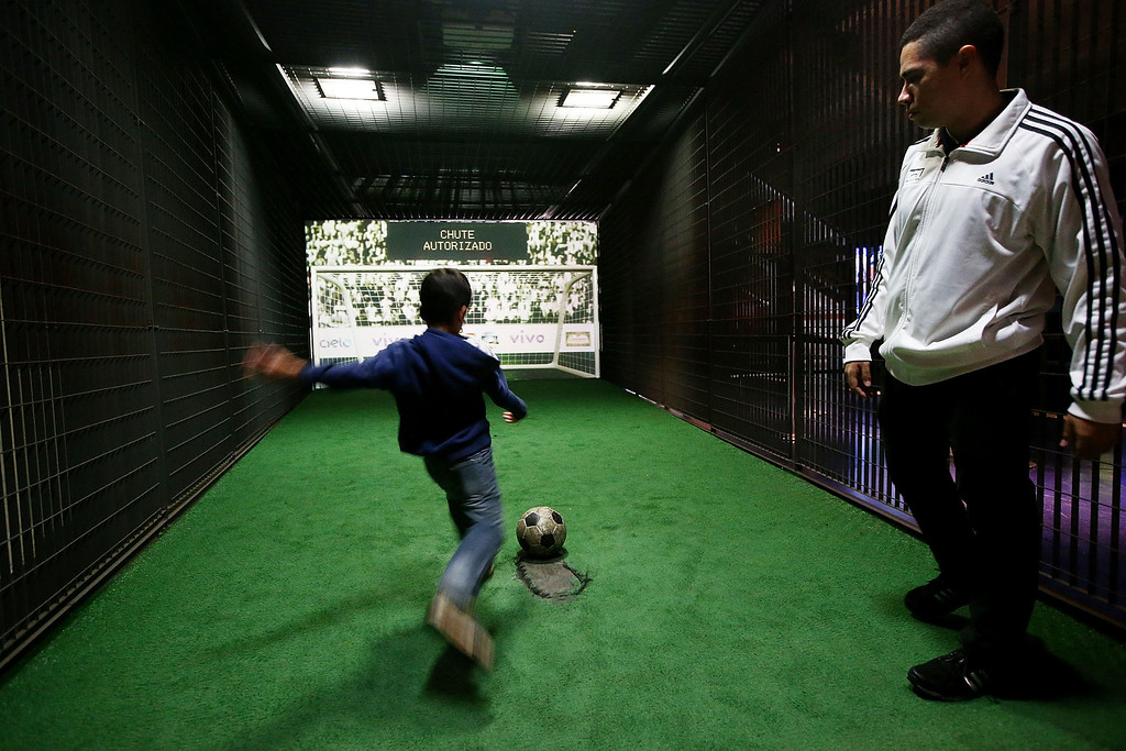 . A boy takes a penalty kick on an interactive goaltender in the Museum of Football on June 10, 2014 in Sao Paulo, Brazil. The museum is housed inside the famed Pacaembu Stadium and hosts exhibits on the history of soccer in Brazil and abroad. The opening match for the 2014 FIFA World Cup is June 12 when Brazil takes on Croatia.  (Photo by Mario Tama/Getty Images)