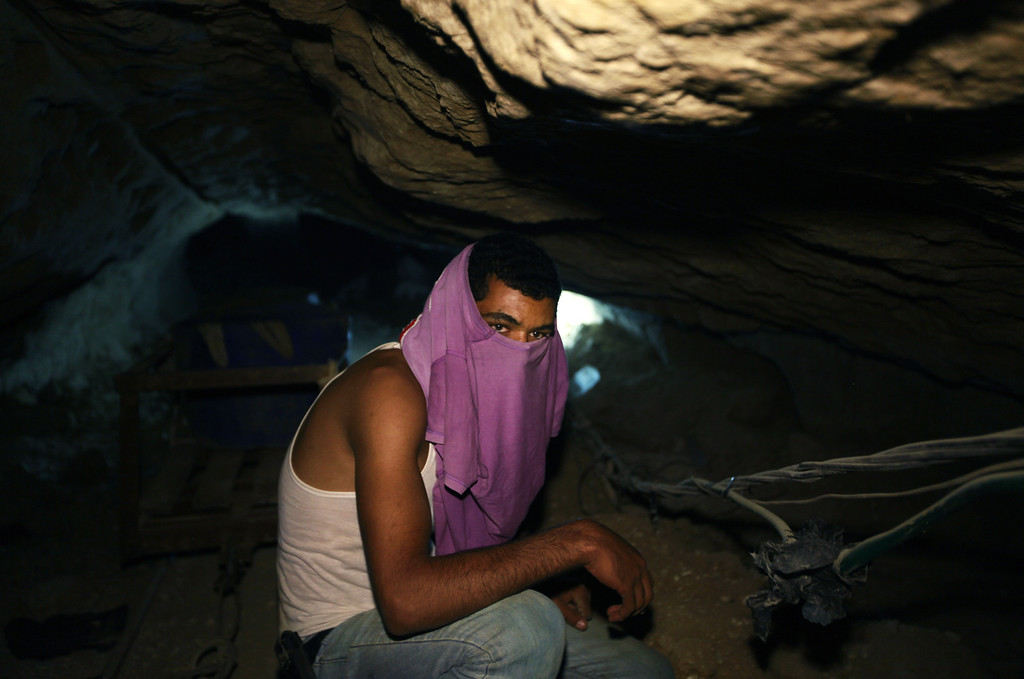 . In this Monday, Sept. 30, 2013 photo, a Palestinian worker sits inside a smuggling tunnel in Rafah, on the border between Egypt and the southern Gaza Strip. Since the summer, Egypt�s military has tried to destroy or seal off most of the smuggling tunnels under the Gaza-Egypt border, a consequence of the heightened tensions between Cairo and the Hamas government in Gaza. The tunnels once employed thousands of young men in Gaza. By early September, with most tunnels closed, only few tunnel workers reported to their jobs for maintenance work. Some mask their faces with shirts to avoid identification while working, for fear of repercussions in case they were to travel to Egypt in the future. (AP Photo/Hatem Moussa)