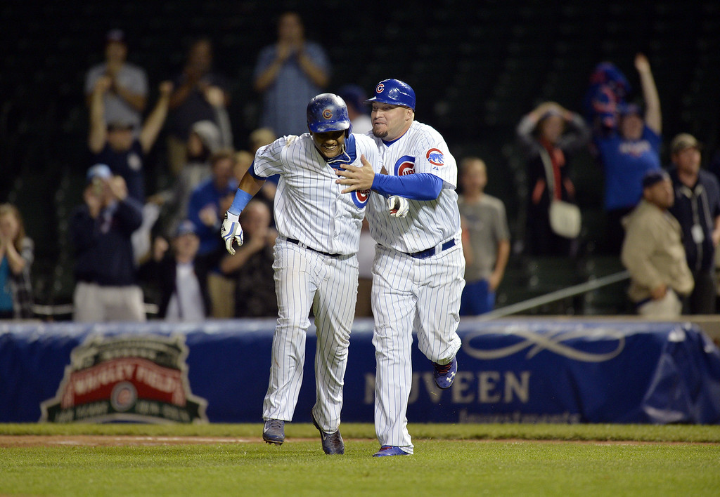 . First base coach Eric Hinske #77 of the Chicago Cubs (R) congratulates Starlin Castro #13 after Castro hit a game-winning RBI single scoring John Baker during the 16th inning against the Colorado Rockies on July 30, 2014 at Wrigley Field in Chicago, Illinois. The Cubs defeated the Rockies 4-3 in 16 innings.  (Photo by Brian Kersey/Getty Images)
