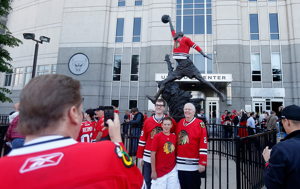 . CHICAGO, IL - JUNE 15:  Chicago Blackhawks fans pose infront of The Michael Jordan statue prior to Game Two of the NHL 2013 Stanley Cup Final against the Boston Bruins at United Center on June 15, 2013 in Chicago, Illinois.  (Photo by Gregory Shamus/Getty Images)