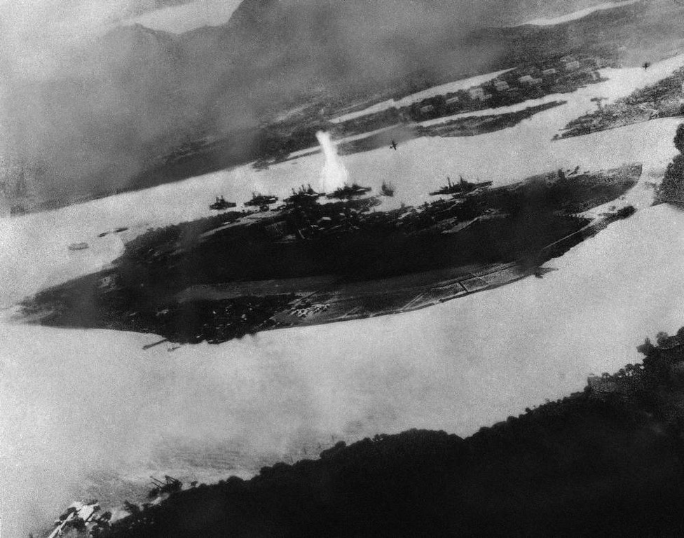 . Believed to be the first bomb dropped on Pearl Harbor, Hawaii in the sneak-attack on Dec. 7, 1941, this picture was found torn to pieces at Yokusuka Base by photographer\'s mate 2/C Martin J. Shemanski of Plymouth, Pa. One Japanese plane is shown pulling out of a dive near bomb eruption (center) and another the air at upper right. (AP Photo)