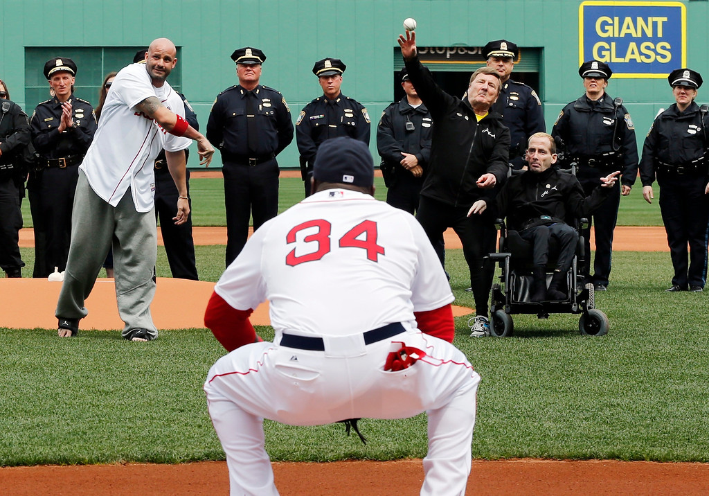 . Boston Marathon bombing victim Steven Byrne, midground left, and marathon runners Dick and Rick Hoyt, midground right, throw out ceremonial first pitches as Boston Red Sox\'s David Ortiz  (34) catches before a baseball game against the Kansas City Royals in Boston, Saturday, April 20, 2013. (AP Photo/Michael Dwyer)