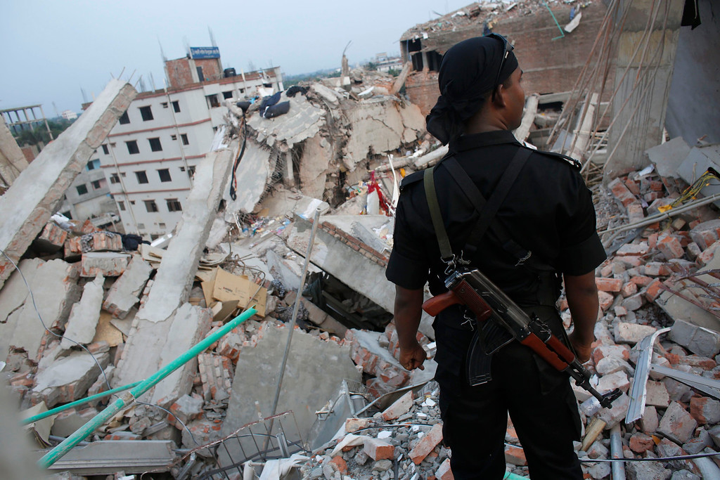 . A member of the Rapid Action Battalion (RAB) stands in front of the rubble of the collapsed Rana Plaza building, in Savar, 30 km (19 miles) outside Dhaka April 27, 2013. Two factory bosses and two engineers were arrested in Bangladesh on Saturday, 72 hours after the collapse of a building where low-cost garments were made for Western brands, as the death toll rose to 340 but many were still being found alive. REUTERS/Andrew Biraj