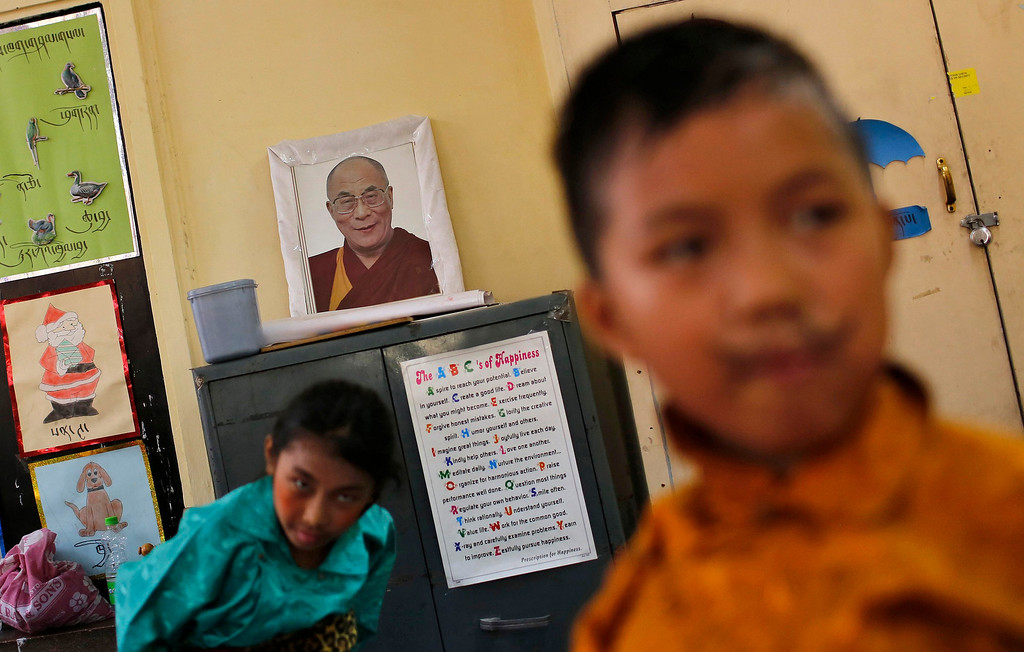 . Tibetan exiles stand next to a portrait of Tibetan spiritual leader Dalai Lama after their performance during celebrations of the spiritual leader\'s 78th birthday at Majnu Ka Tila, a Tibetan refugee camp in New Delhi July 6, 2013. REUTERS/Adnan Abidi