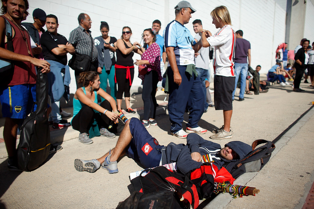 . Nicolas, an Argentine tourist, takes a nap as he waits with friends in line outside Independencia Stadium for free tickets to watch a practice session by Argentina\'s soccer team in Belo Horizonte, Brazil, Tuesday, June 10, 2014. The World Cup starts on June 12. (AP Photo/Victor R. Caivano)