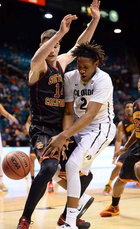 . Xavier Johnson #2 of the Colorado Buffaloes loses the ball as he drives against Strahinja Gavrilovic #14 of the USC Trojans during a first-round game of the Pac-12 Basketball Tournament at the MGM Grand Garden Arena on March 12, 2014 in Las Vegas, Nevada.  (Photo by Ethan Miller/Getty Images)