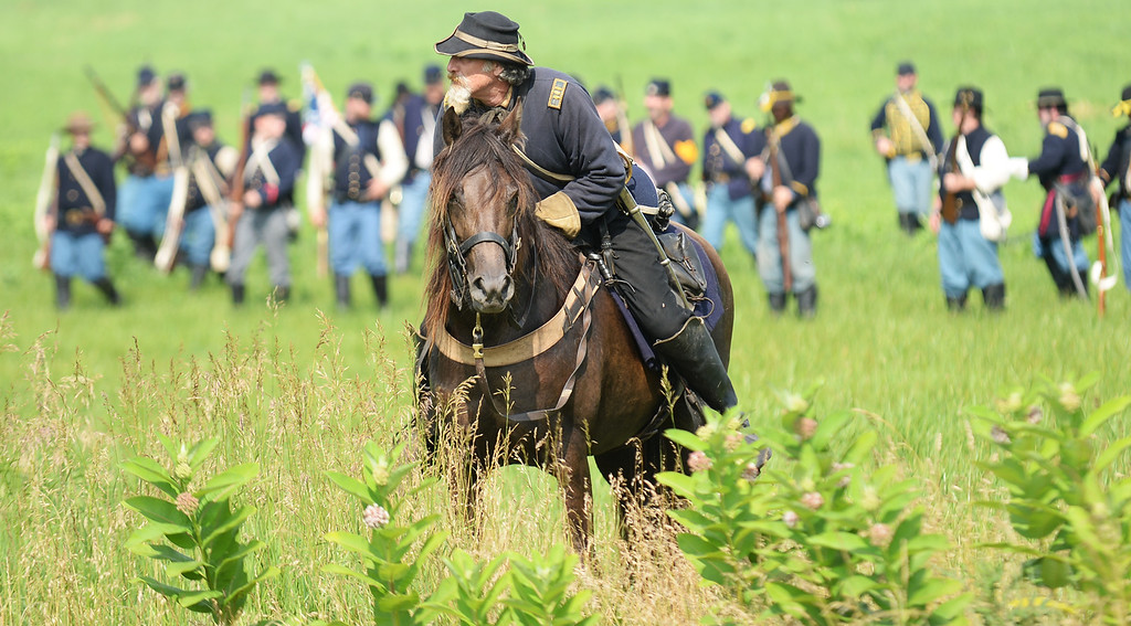 """. A Union solider dodges \""""bullets\"""" while on horseback during the Blue-Grey Alliance event at the Bushey Farm on June 28, 2013. LEBANON DAILY NEWS - JEREMY LONG"""