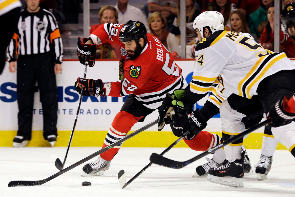 . Chicago Blackhawks left wing Brandon Bollig (52) controls the puck against Boston Bruins defenseman Adam McQuaid (54) and Torey Krug during the second period of Game 1 in their NHL Stanley Cup Final hockey series, Wednesday, June 12, 2013, in Chicago. (AP Photo/Nam Y. Huh)