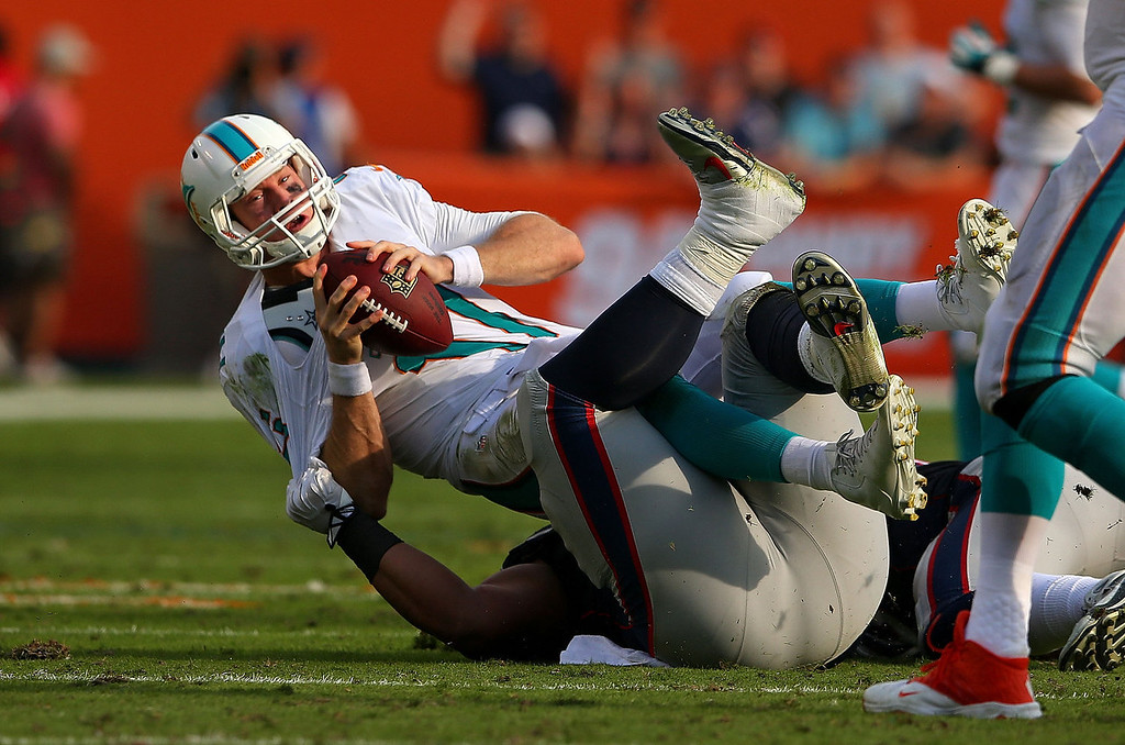. Ryan Tannehill #17 of the Miami Dolphins is sacked by Sealver Siliga #71 of the New England Patriots during a game  at Sun Life Stadium on December 15, 2013 in Miami Gardens, Florida.  (Photo by Mike Ehrmann/Getty Images)
