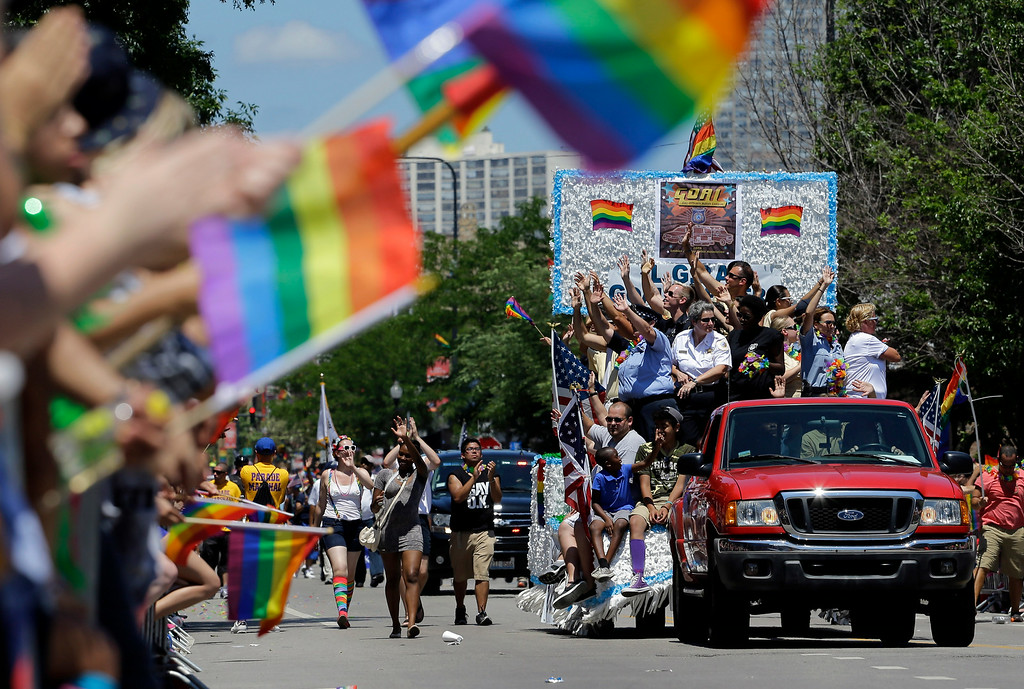 . Police officers ride a float in the 45th Annual Chicago Pride Parade  in Chicago, Sunday, June 29, 2014. The event, the first since Illinois\' law allowing same-sex marriage went into effect, has 200 registered entrants, with about 1 million expected to participate. (AP Photo/Nam Y. Huh)