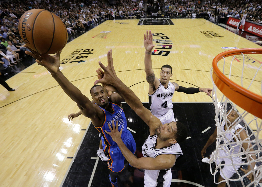 . Oklahoma City Thunder\'s Kendrick Perkins shoots over San Antonio Spurs\' Tim Duncan, right, during the first half of Game 5 of the Western Conference finals NBA basketball playoff series, Thursday, May 29, 2014, in San Antonio. (AP Photo/Eric Gay)